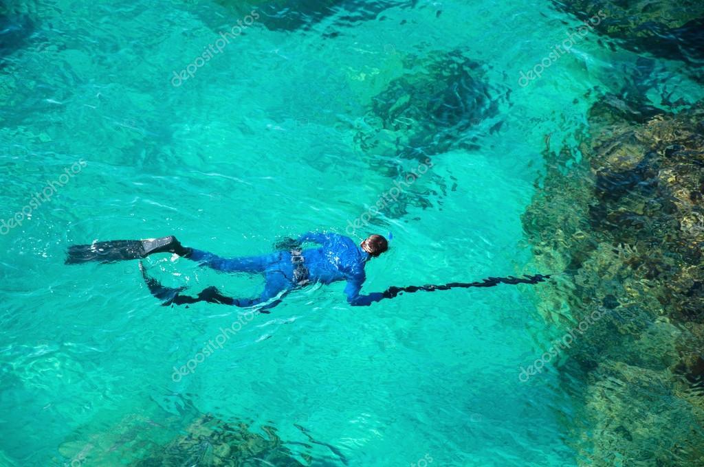 Emerald green sea water diver spearfishing