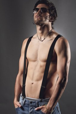 Studio shot of a sexy man with black suspenders and sunglasses