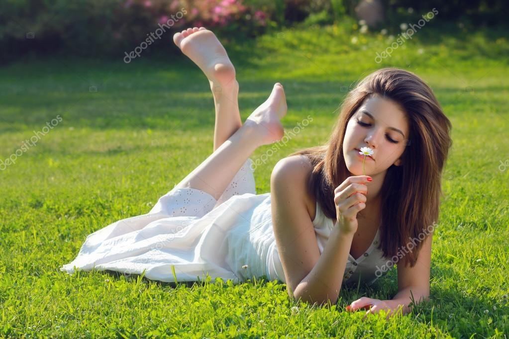 Attractive young girl with daisy lying on grass