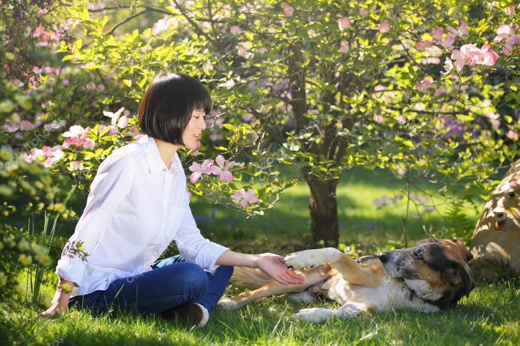 Girl  touching her dog paw