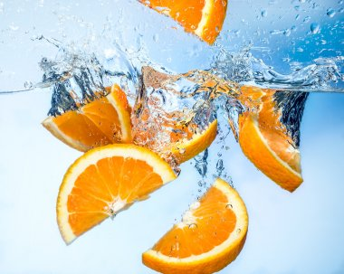 Orange fruits fall deeply under water with a big splash