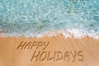 Holidays sign on sand