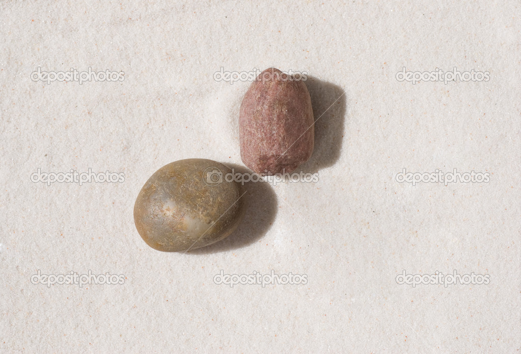 Two stones lying on the sand