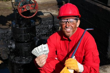 Satisfied Worker Holding Money at Oil Field