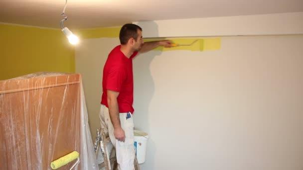 Mann auf Leiter malte Wand