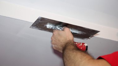Construction Worker Plastering Ceiling With Work Tool