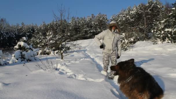 muž hraje se svým psem se sněhem na Zimní krajina