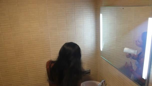 krásná žena, sušení vlasy s vysoušečem vlasů v koupelně