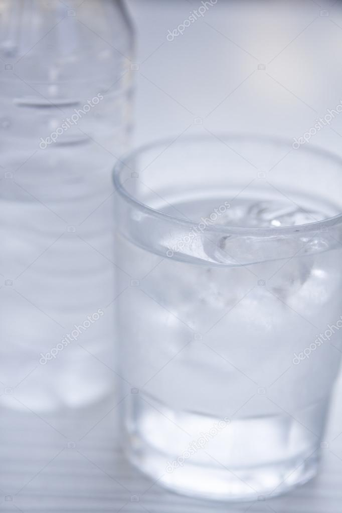 fresh cold clear mineral water in bottle and glass on table stock