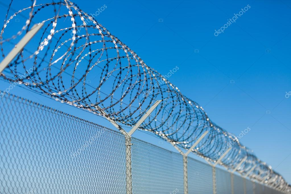 Coiled razor wire on top of a fence — Stock Photo © nilswey #43219015