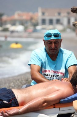 Masseur giving a full massage to a male on the beach