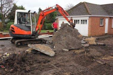 A mini digger excavating a driveway