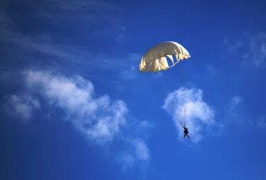 single parachute jumper against blue sky background