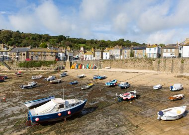 Boats in Mousehole harbour Cornwall England Cornish fishing village with blue sky and clouds at low tide