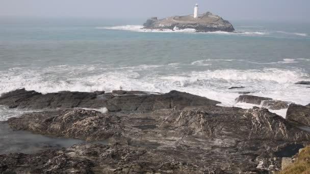 Leuchtturm und Insel mit Meer brechen über Felsen Godrevy Cornwall England uk