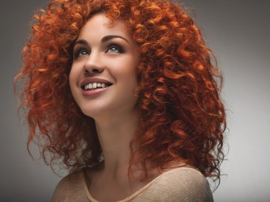 Red Hair. Beautiful Woman with Curly Long Hair. High quality ima