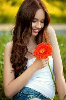 Beautiful Woman With Gerbera Flower Enjoying Nature against Natu