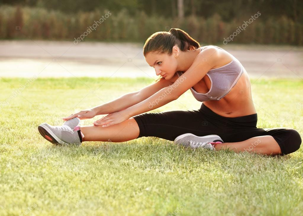 Beautiful Woman doing Stretching Exercise against Nature Background
