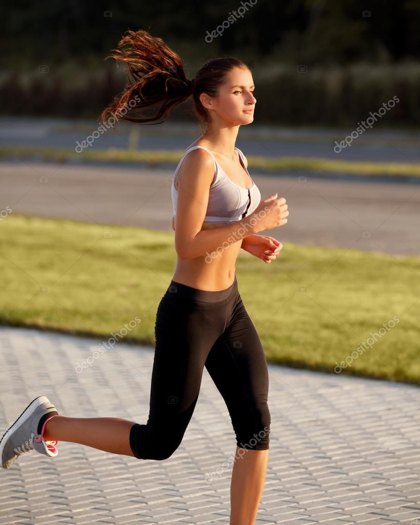 Athletic Runner Training in a park for Marathon. Fitness Girl Running outdoors