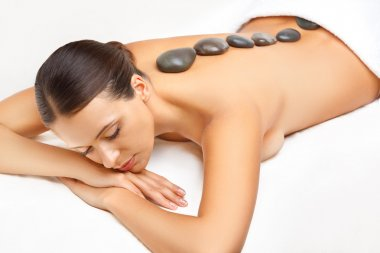 Stone Massage. Beautiful Woman Getting Spa Hot Stones Massage in