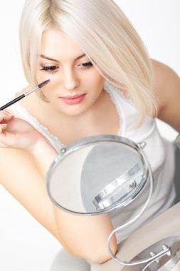 Woman applying mascara on eyelashes.
