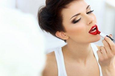Brunette applies lipstick