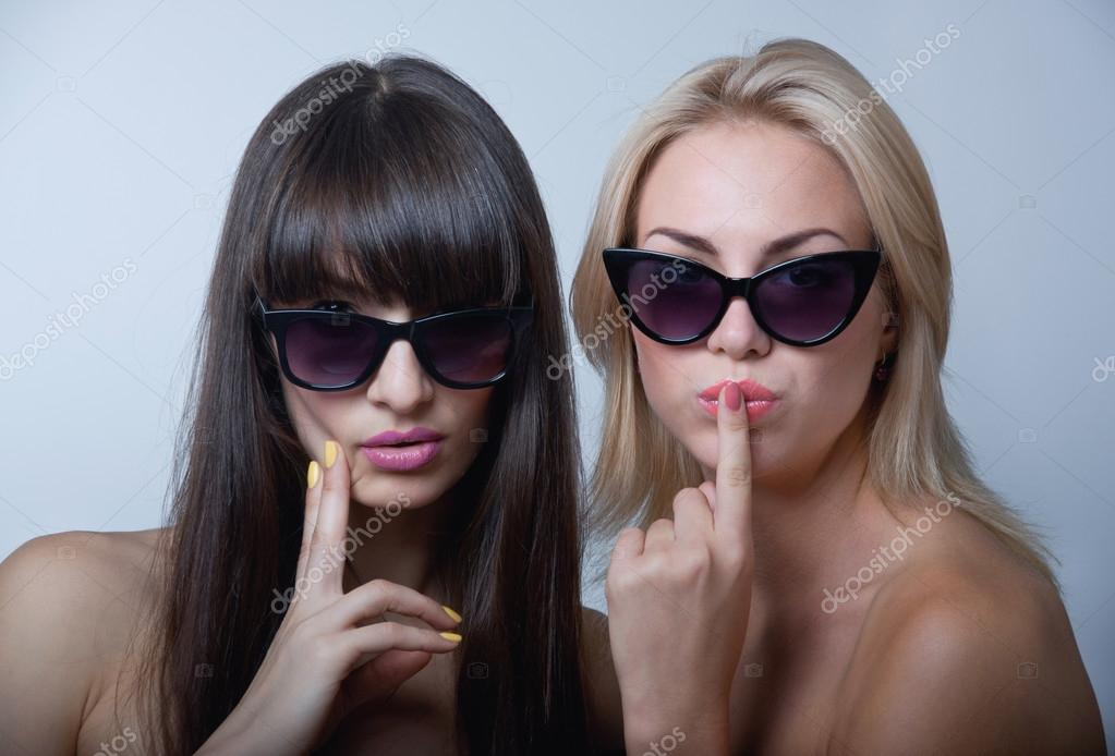 17a6e8b301 Retrato de estudio de dos lindas hermosas mujeres jóvenes modelos con los  anteojos de sol, tomados de las manos cerca de los labios y el mentón, ...