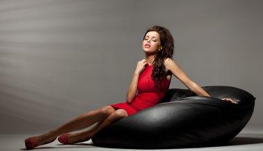 Sexy brunette woman lies on the black pillow