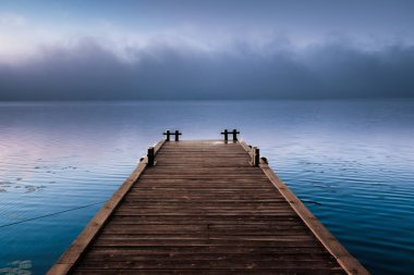 Wooden pier near beautiful fog cloud in morning river