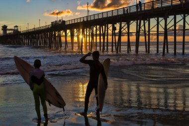 Surfers watch an Oceanside California sunset.
