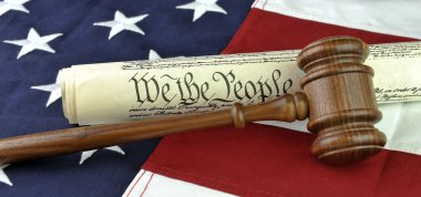 US constitution with judge's gavel over American flag background