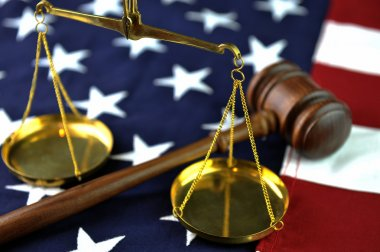 Gavel and scales atop flag background