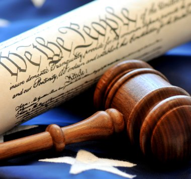 Closeup of gavel with constitution and flag in background.