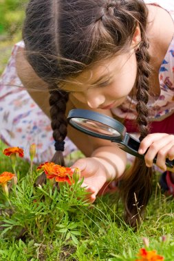 girl sees flowers through magnifying glass
