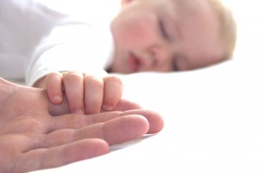 Sleeping boy is holding father's hand