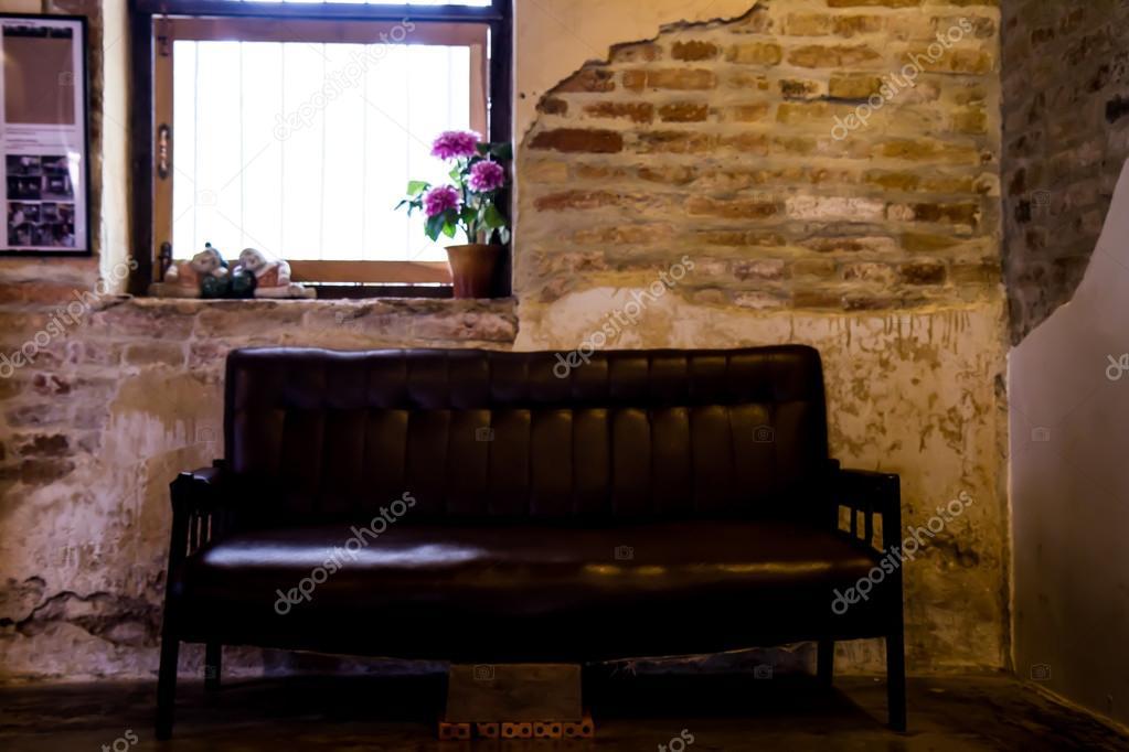 Divano nero le vecchie pareti in muratura. — Foto Stock ...