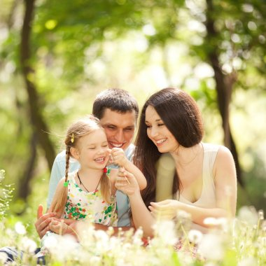 Happy mother, father and daughter playing in the park