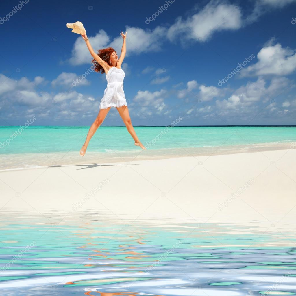 Happy Young Woman In White Dress With Hat Jumping On The
