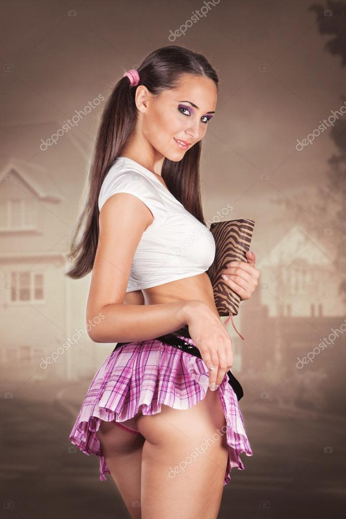 Sexy schoolgirl holding a book and lifting her skirt showing but