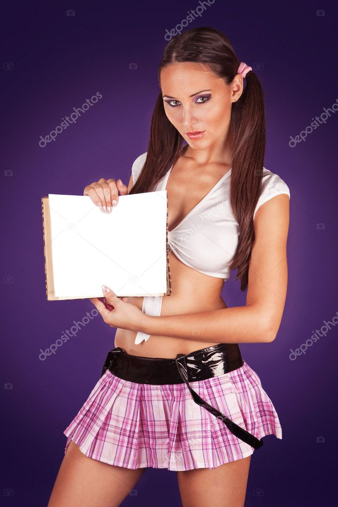 Sexy schoolgirl holding an open book showing a blank paper copys