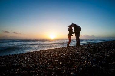 Romantic photo of kissing couple during sunset