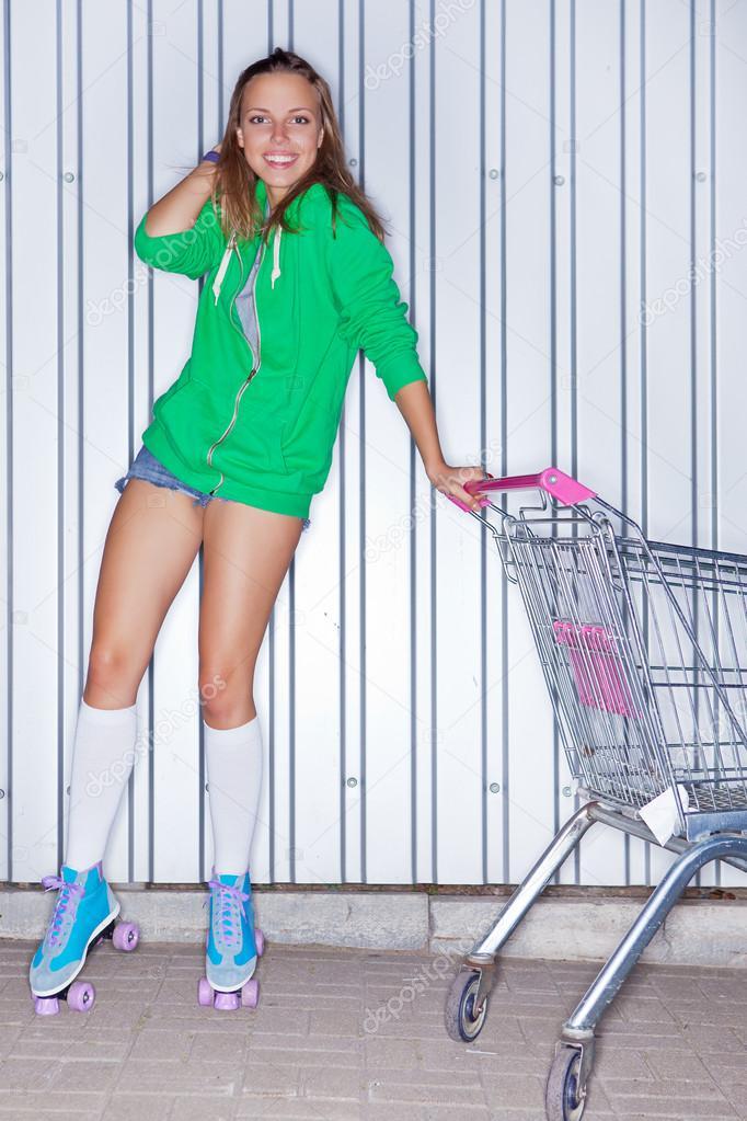 ein sch nes junges m dchen in roller scates in der n he von supermarkt trolley stockfoto. Black Bedroom Furniture Sets. Home Design Ideas