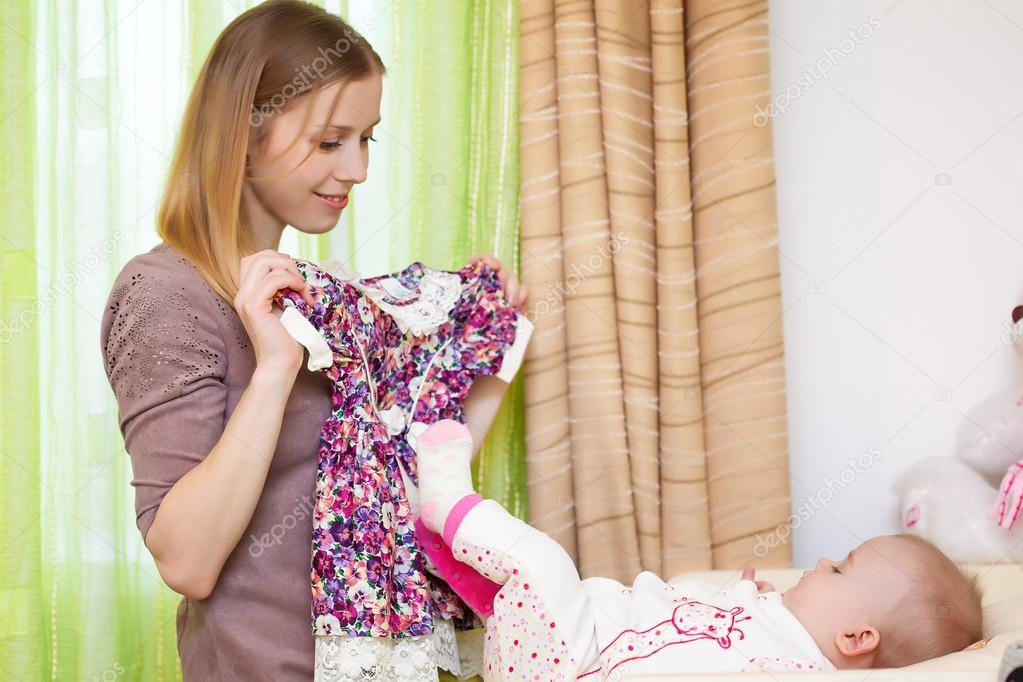 Young mother is showing a dress for her daughter