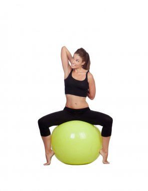 Young beautiful woman sitting on a gymnastic ball stretching arm