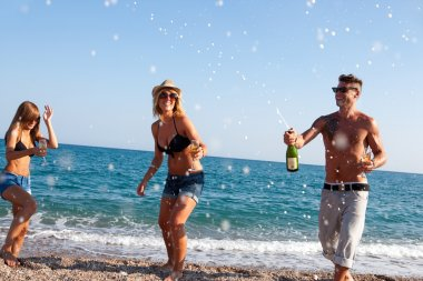 Dancing under champagne bubbles on beach.