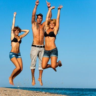 Group of young friends jumping on beach.