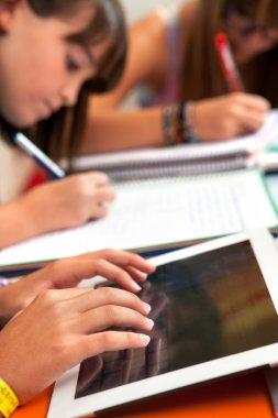 Girls hands on tablet at homework session.