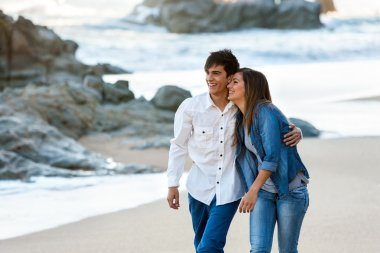 Cute teen couple walking along beach.