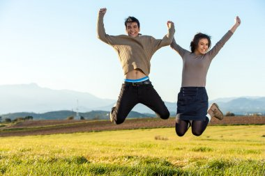 Teen couple jumping outdoors.