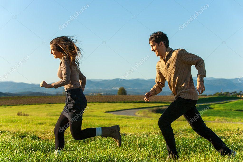 Happy couple having a race outdoors.